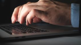 Close up hands of businessman typing text on laptop keyboard at desk in office. Male arms of manager working on notebook stock video