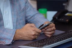 Close-up hands of businessman using mobile phone at office. Royalty Free Stock Photo