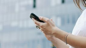 Close-up of hands of a businesswoman holding modern mobile phone, woman texting messages, chatting with friends stock footage