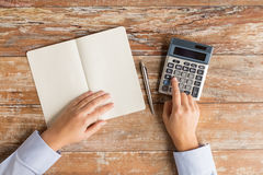 Close up of hands with calculator and notebook Royalty Free Stock Image
