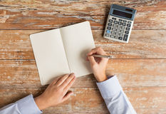 Close up of hands with calculator and notebook Stock Images