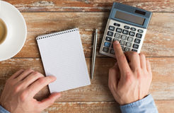 Close up of hands with calculator and notebook Royalty Free Stock Images