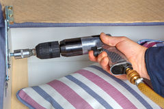 Close-up hands of a carpenter with pneumatic wrench. Royalty Free Stock Image