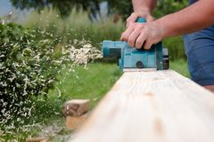 Close up hands of carpenter working with electric planer on wooden plank stock image