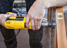 Close-up of hands carpenter with yellow drill drilled hole lock. Stock Images