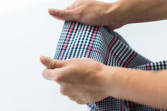 Close up of hands with checkered clothing item. Laundry, clothes, fashion and people concept - close up of hands with checkered clothing item Royalty Free Stock Photography