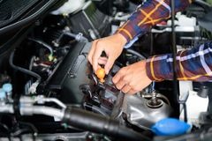 Close up hands checking lube oil level of car engine from deep-s Royalty Free Stock Photo