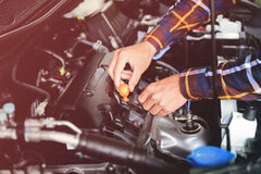 Close up hands checking lube oil level of car engine from deep-s Royalty Free Stock Image