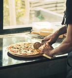 Close up of hand Chef black shirt cutting freshly baked pizza. Close up of hands Chef black shirt cutting freshly baked pizza, some ingredients flour around on Royalty Free Stock Photography