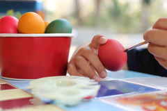 Close up hands of child coloring eggs with paintbrush for preparing Easter day on nature blurred background. Royalty Free Stock Photography
