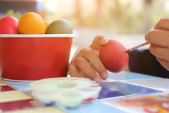 Close up hands of child coloring eggs with paintbrush for preparing Easter day on nature blurred background. Sunshine effect. Stock Image