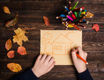Close up of the hands of a child drawing a house on dark wooden. Rustic table covered with autumn leaves. Top view. Family house concept royalty free stock photography