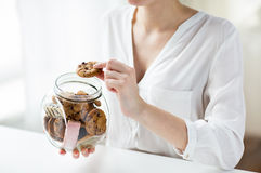 Close up of hands with chocolate cookies in jar Royalty Free Stock Photos