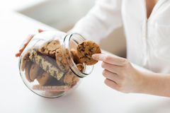 Close up of hands with chocolate cookies in jar Stock Photos