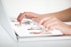 Close up of hands choosing pictures on a futuristic laptop Stock Photography