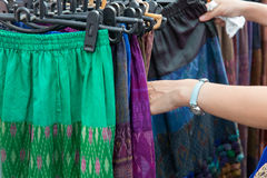Close up of hands choosing skirts at street market Stock Photos