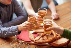 Close up of hands clinking beer at bar or pub Royalty Free Stock Photo