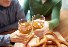 Close up of hands clinking beer at bar or pub Stock Photography