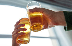Close up of hands clinking beer glasses at pub Stock Images