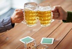 Close up of hands clinking beer mugs at bar or pub Stock Images