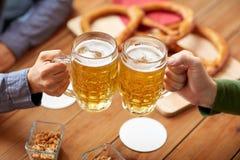 Close up of hands clinking beer mugs at bar or pub Royalty Free Stock Image