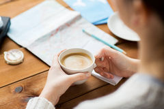 Close up of hands with coffee cup and travel stuff Royalty Free Stock Photo