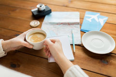 Close up of hands with coffee cup and travel stuff Stock Photos