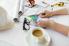 Close up of hands with color palette and blueprint. Business, architecture, building, construction and people concept - close up of designer hands with color Royalty Free Stock Image