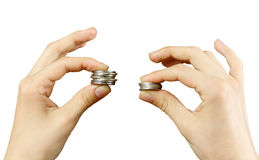 Close up. Hands compare two piles of coins of different sizes, i Stock Photos