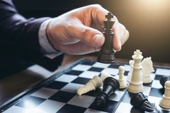 Close up of hands confident businessman colleagues playing chess Royalty Free Stock Image