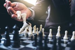 Close up of hands confident businessman colleagues playing chess Stock Images