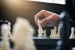 Close up of hands confident businessman colleagues playing chess Royalty Free Stock Photos