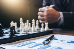 Close up of hands confident businessman colleagues playing chess Stock Photo