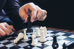 Close up of hands confident businessman colleagues playing chess Stock Image