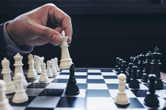 Close up of hands confident businessman colleagues playing chess Stock Photography