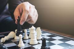 Close up of hands confident businessman colleagues playing chess Royalty Free Stock Images