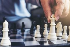 Close up of hands confident businessman colleagues playing chess Stock Photos