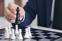 Close up of hands confident businessman playing chess game to de Royalty Free Stock Photos