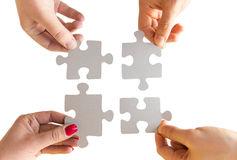 Close up of hands connecting puzzle pieces. Business, teamwork, cooperation, compatibility and connection concept - close up of hands connecting puzzle pieces stock photography