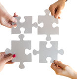 Close up of hands connecting puzzle pieces Stock Photo