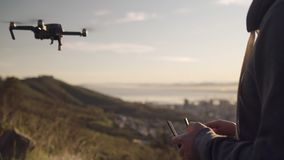 Close up of hands controlling a drone using the remote control as it flies over the city in the early hours of the