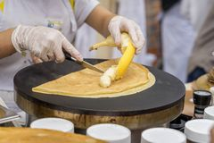 Close-up of hands of cook in gloves preparing Crepe, pancake with fresh banana. Healthy fresh food. Concept national. Close-up of hands of cook in gloves stock photo