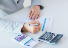 Close up of hands counting money with calculator Royalty Free Stock Photo