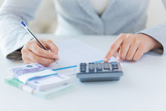 Close up of hands counting money with calculator Royalty Free Stock Images