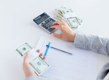Close up of hands counting money with calculator Royalty Free Stock Photos