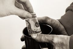 Close-up hands with cup Dirty hands of a beggar homeless man and a dollar bill of alms. royalty free stock image
