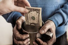 Close-up hands with cup Dirty hands of a beggar homeless man and a dollar bill of alms. Close-up hands with cup Dirty hands of a beggar homeless man and a stock photos