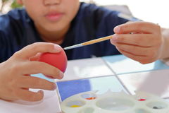 Close up hands of cute boy painting  egg with paintbrush for preparing Easter day. Royalty Free Stock Photo