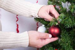 Close up of hands decorating Christmas tree Stock Photography