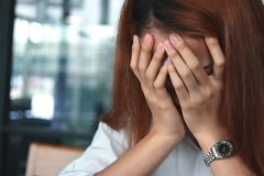 Close up hands of depressed stressed young Asian woman covering face royalty free stock photo